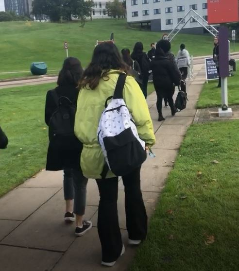 students walking to and under the archway